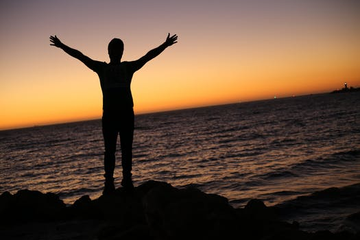 man on beach with arms raised up at a sunset